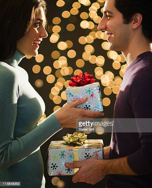 USA, New Jersey, Jersey City, Young couple giving Christmas presents each other