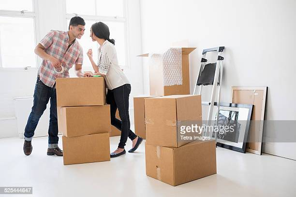 USA, New Jersey, Jersey City, Young couple standing among boxes in new home