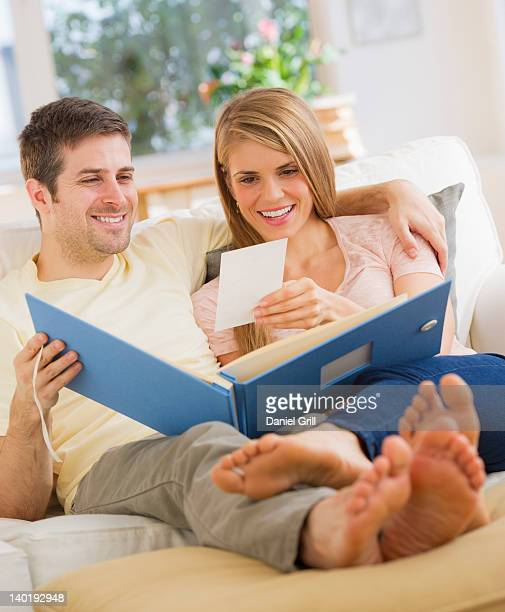 USA, New Jersey, Jersey City, Young couple watching photos on sofa