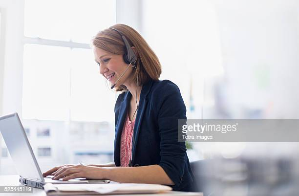 USA, New Jersey, Jersey City, Young office worker talking on headset and typing