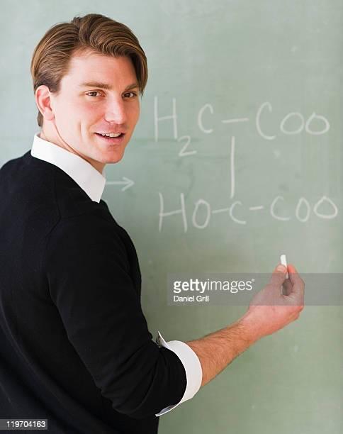 USA, New Jersey, Jersey City, young teacher writing equation on blackboard