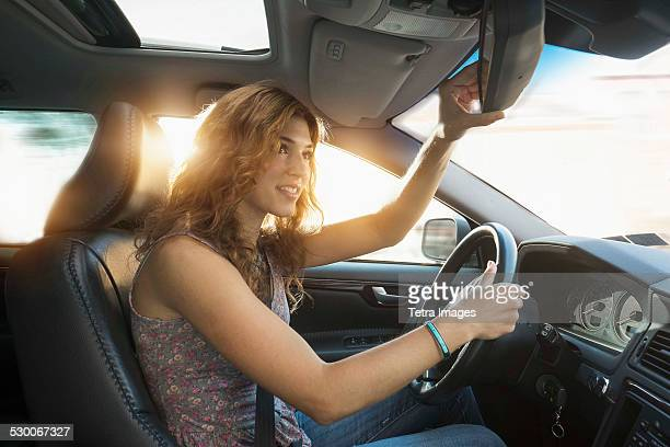 USA, New Jersey, Jersey City, Young woman adjusting rear view mirror while driving
