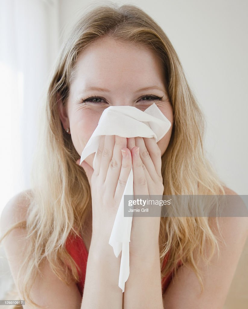 USA, New Jersey, Jersey City, Young woman blowing nose