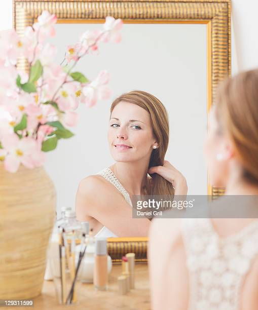 USA, New Jersey, Jersey City, Young woman brushing hair in front of mirror