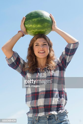 USA, New Jersey, Jersey City, Young woman carrying on head watermelon