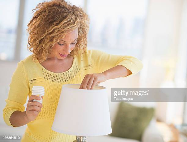 USA, New Jersey, Jersey City, Young woman changing bulb in lamp