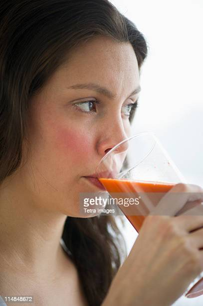 USA, New Jersey, Jersey City, Young woman drinking carrot juice