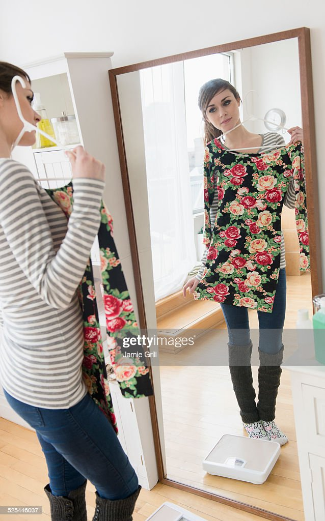 USA, New Jersey, Jersey City, Young woman fitting dress in front of mirror