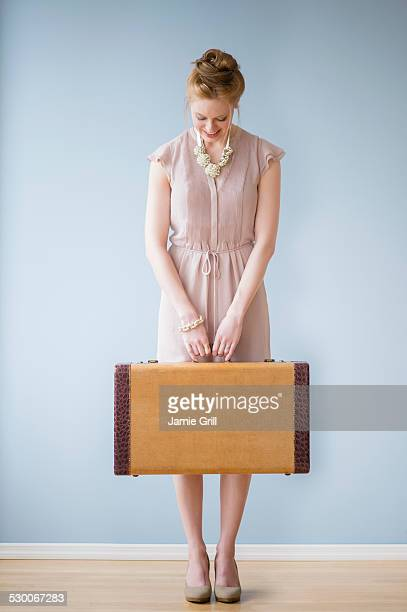 USA, New Jersey, Jersey City, Young woman holding suitcase