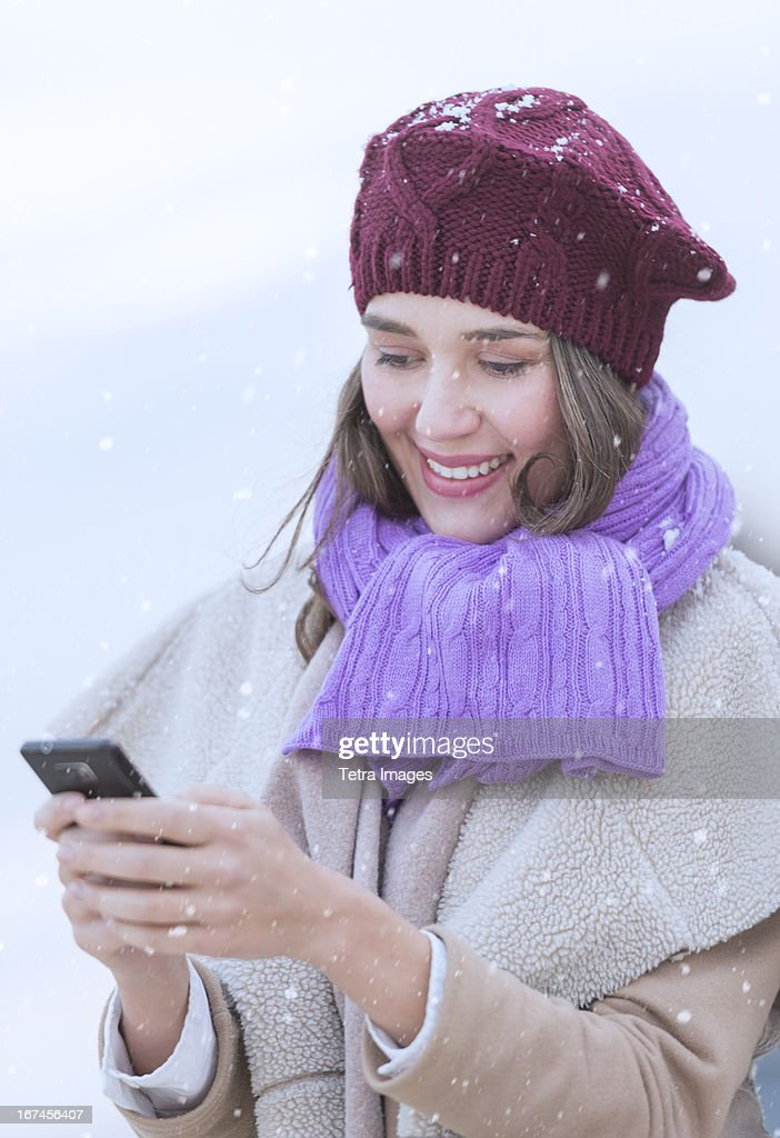 USA, New Jersey, Jersey City, Young woman in wearing warm clothes and using mobile phone : Stock Photo