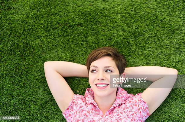 USA, New Jersey, Jersey City, Young woman lying on grass