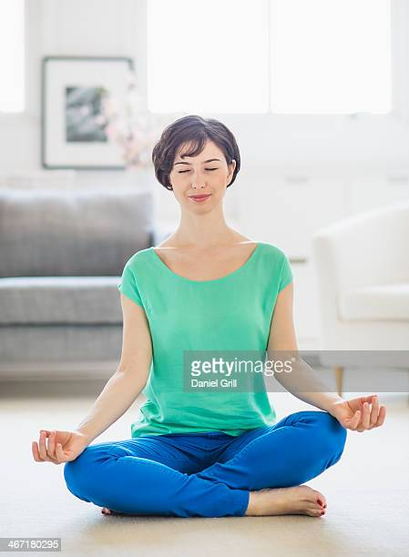 USA, New Jersey, Jersey City, Young woman meditating at home