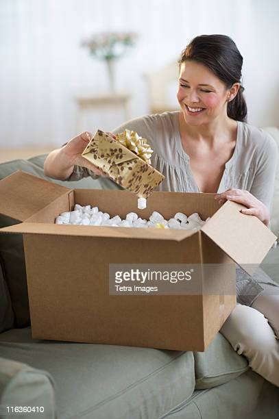 USA, New Jersey, Jersey City, young woman opening box with gift