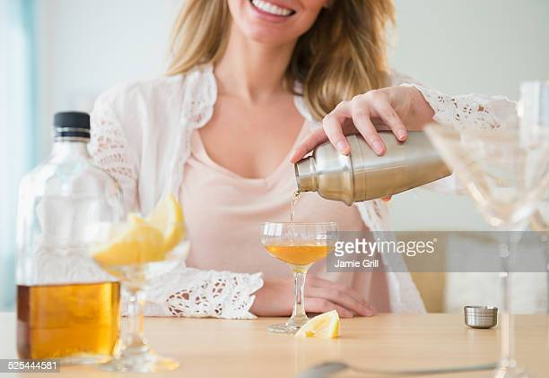 USA, New Jersey, Jersey City, Young woman pouring coctail