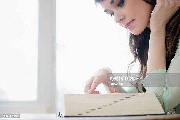 USA, New Jersey, Jersey City, Young woman reading dictionary