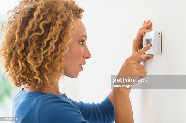 USA, New Jersey, Jersey City, Young woman setting air conditioning