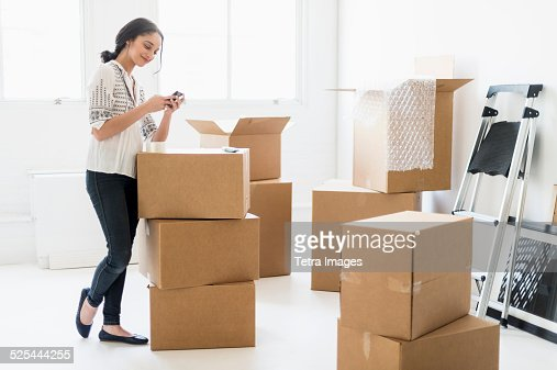 USA, New Jersey, Jersey City, Young woman standing among boxes in new home and using mobile phone