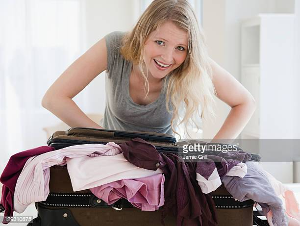 USA, New Jersey, Jersey City, Young woman trying to close luggage