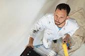 USA, New Jersey, Man climbing ladder with paint roller