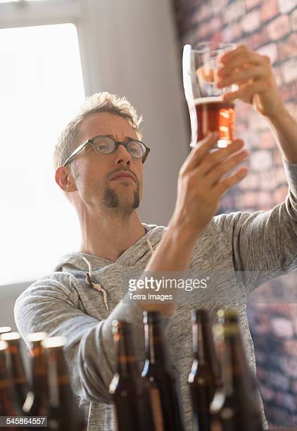 USA, New Jersey, Man examining glass of beer