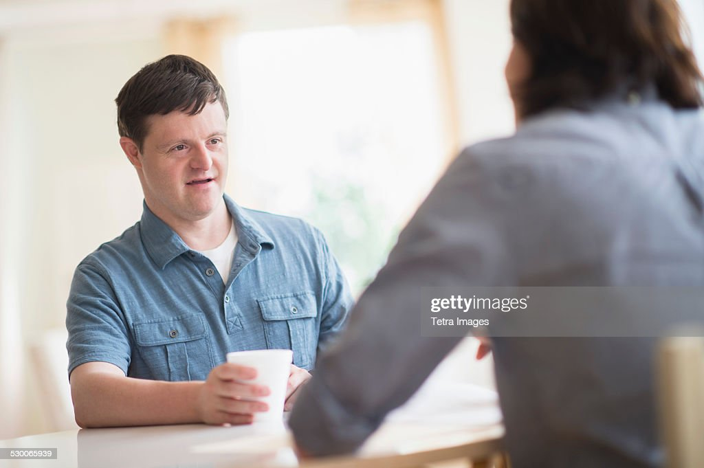 USA, New Jersey, Man with down syndrome talking with care taker