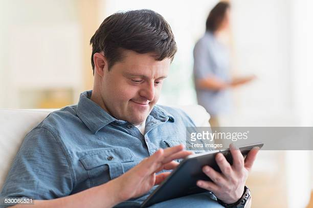 USA, New Jersey, Man with down syndrome using tablet