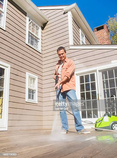 USA, New Jersey, Mendham, Portrait of man cleaning porch