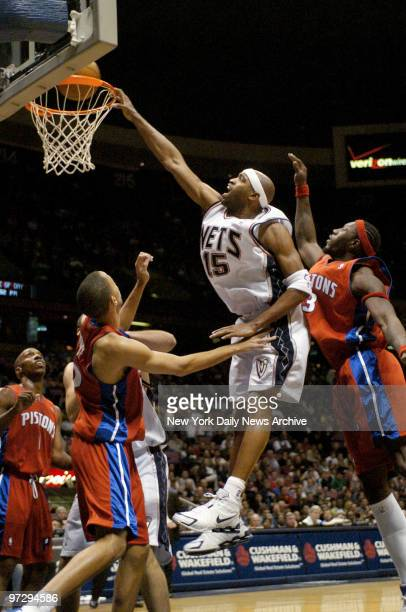 New Jersey Nets' Vince Carter dunks against Detroit Pistons' Tayshaun Prince and Ben Wallace in the first half at Continental Airlines Arena The...
