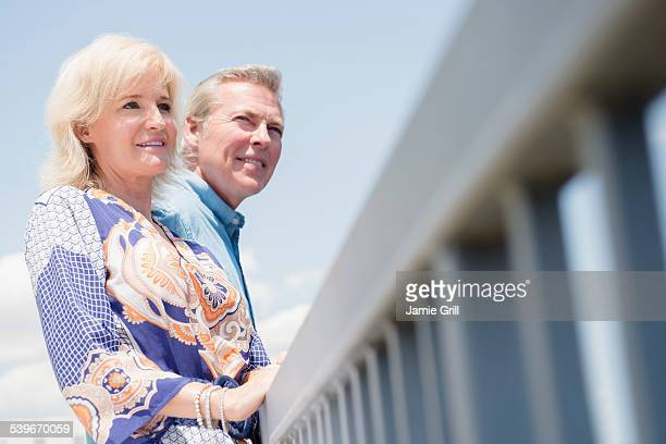 USA, New Jersey, Portrait of couple leaning at railing, looking at view
