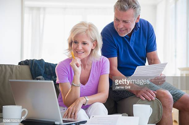 USA, New Jersey, Portrait of couple sitting on sofa using laptop