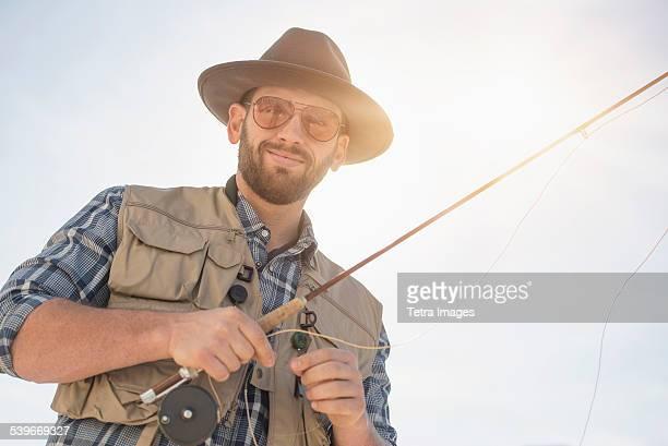 USA, New Jersey, Portrait of man holding fishing rod