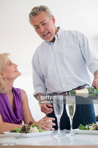 USA, New Jersey, Portrait of man pouring champagne at restaurant table