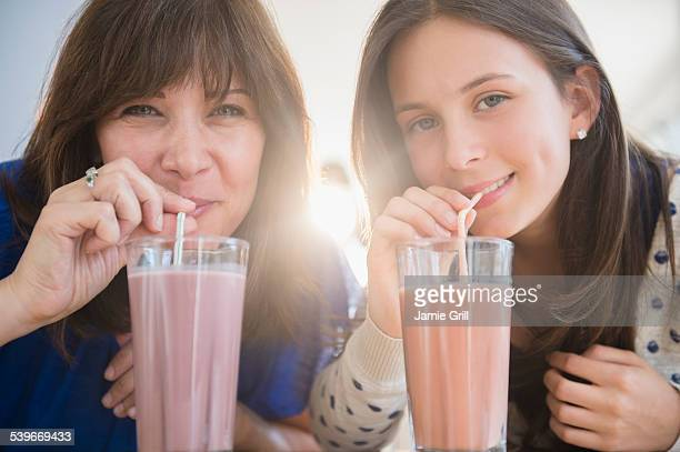 USA, New Jersey, Portrait of mother and daughter (14-15) drinking milkshakes
