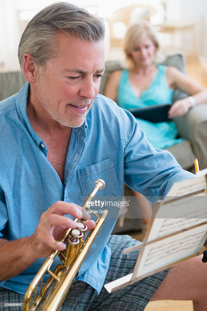 USA, New Jersey, Portrait of senior man holding trumpet looking at music stand with woman on sofa in background