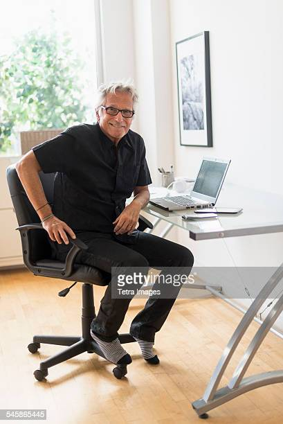 USA, New Jersey, Portrait of smiling senior man sitting in home office