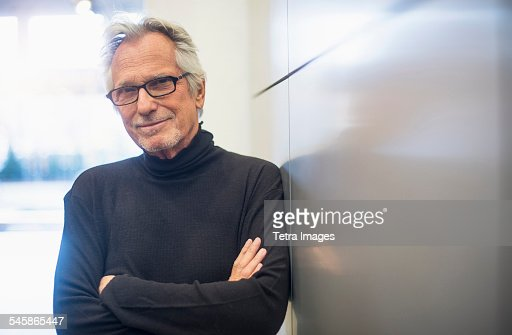 USA, New Jersey, Portrait of smiling senior man standing in office corridor