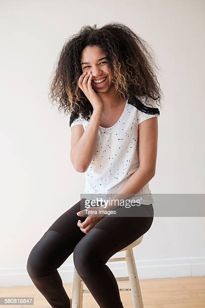 USA, New Jersey, Portrait of teenage girl (16-17) sitting on stool