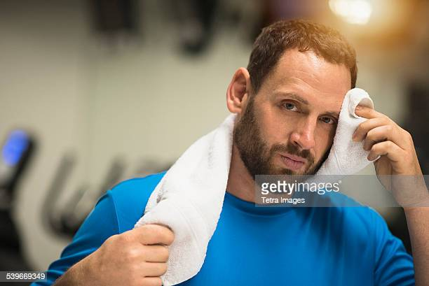 USA, New Jersey, Portrait of tired man wiping face with towel