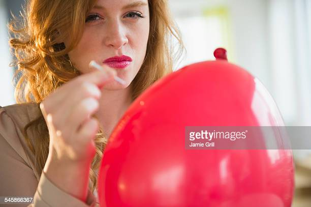 USA, New Jersey, Portrait of young woman popping balloon