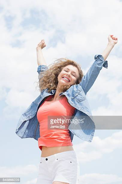 USA, New Jersey, Portrait of young woman with arms raised