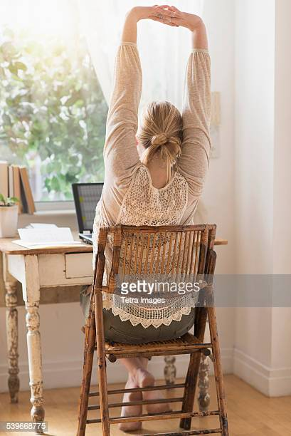 USA, New Jersey, Rear view of woman stretching in front of laptop