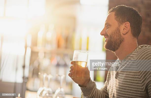 USA, New Jersey, Side view of man having drink in bar