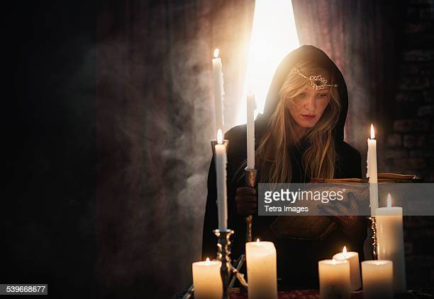 USA, New Jersey, Sorceress reading book in dark room