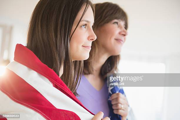 USA, New Jersey, Teenage girl (14-15) and her mom wrapped in American Flag on Fourth of July