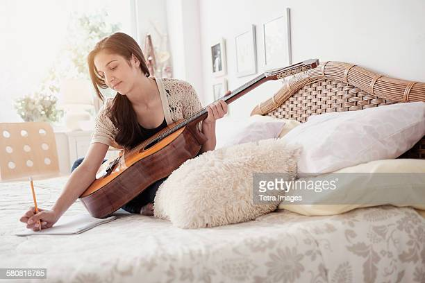 USA, New Jersey, Teenage girl (14-15) playing guitar