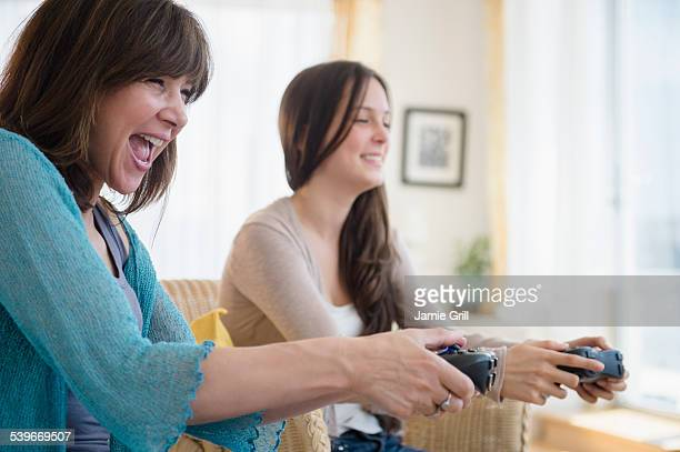 USA, New Jersey, Teenage girl (14-15) playing video games with her mom