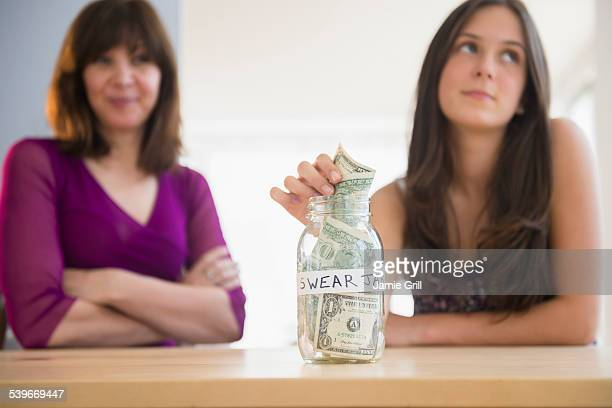 USA, New Jersey, Teenage girl (14-15) putting money in swear jar