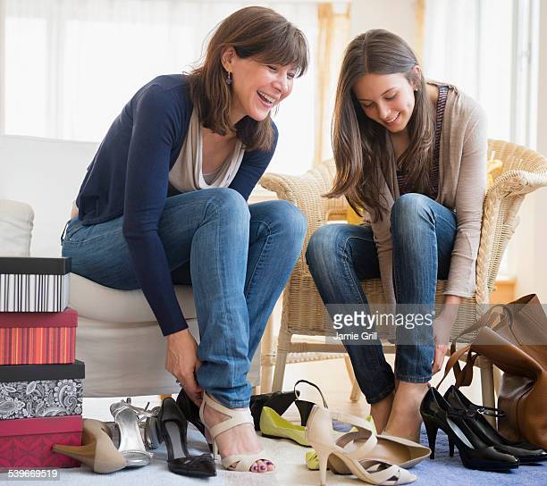 USA, New Jersey, Teenage girl (14-15) sitting with her mom and trying on high heels