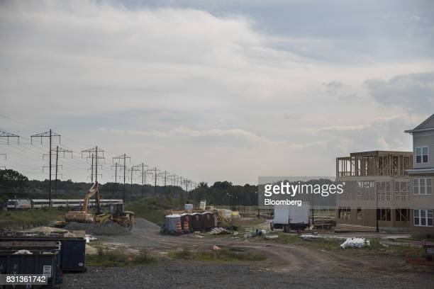 A New Jersey Transit train passes in front of townhouses under construction in North Brunswick New Jersey US on Thursday Aug 10 2017 Between US Route...