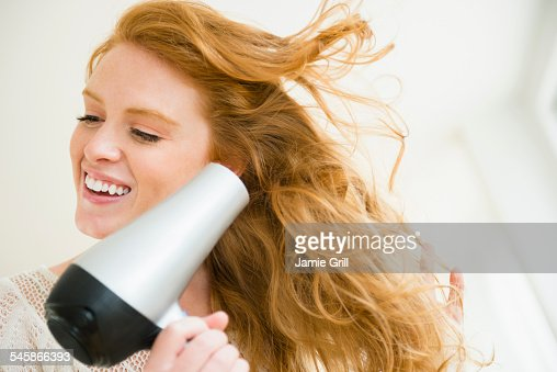 USA, New Jersey, Woman blow drying hair